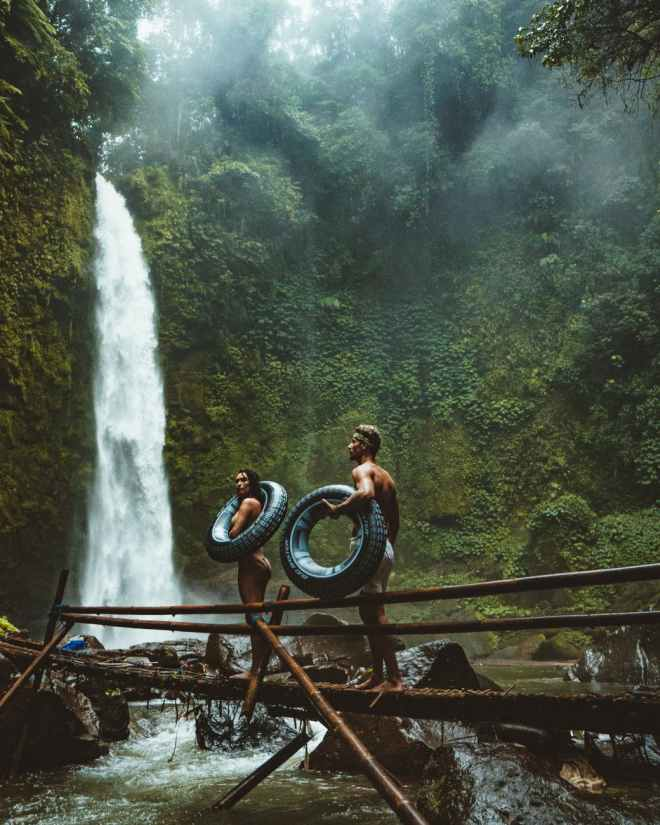 two person carrying black inflatable pool float on brown wooden bridge near waterfalls